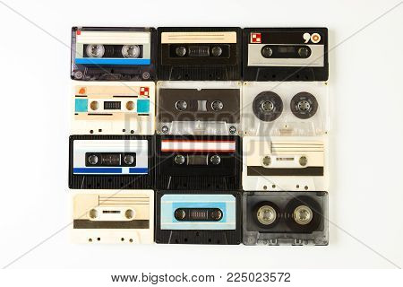 Group of retro audio cassettes isolated on white background, close-up, top view. Tape and audio, music and sound, media and record