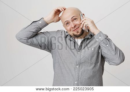 Studio portrait of pleased and happy bald adult male scratching his head while talking on smartphone, standing over gray background. Guy is flattered to receive call from his coworkers on b-day.
