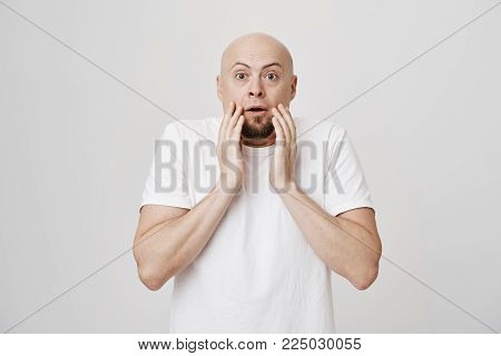 Shocked and surprised bald bearded father holding hands near mouth and look with widened eyes at camera, standing over gray background. guy can not believe terrible situation happened in front of him.