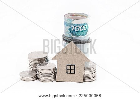 Cardboard house, coins and bills on a white background