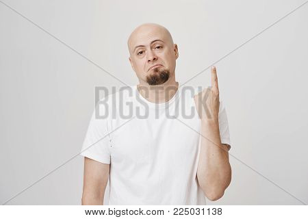 Portrait of gloomy and unsatisfied bald european man with beard showing index finger or number one, expressing disappointment and looking gloomy at camera over gray background. Emotions concept