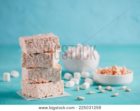 Homemade square bars of marshmallow and crispy rice with ingredients on azure blue background. Stack of American dessert with marshmallow and crispy rice. Copy space