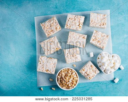Homemade square bars of Marshmallow and crispy rice and ingredients on blue background. American dessert with marshmallow and crispy rice. Top view. Copy space