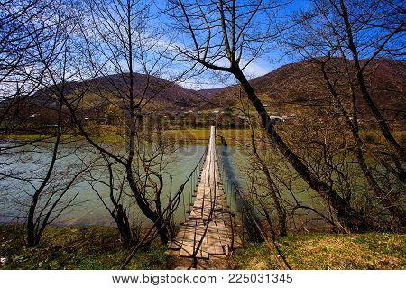 Suspension bridge. Old pendant bridge over river. Wooden long rope bridge cross the stream in the village