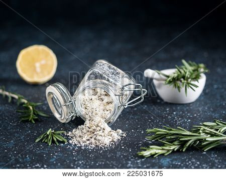 Sea salt scented herb rosemary and lemon zest. Sea salt with aromatic herb spilled out of glass jar on dark blue background. Scented salt and ingerdients - fresh rosemary and lemon. Copy space