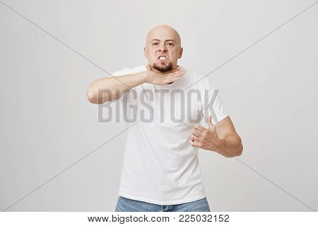 Portrait of angry annoyed bald man with beard gesturing as if cutting neck, showing that he is fed up and quit, standing over gray background. I am sick and tired of this job. Enough of this bullshit.