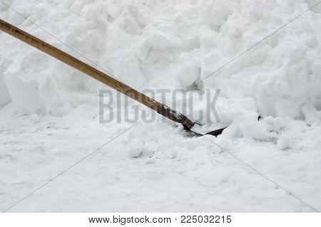 Shovel stuck in bank of snow at winter snowdrift