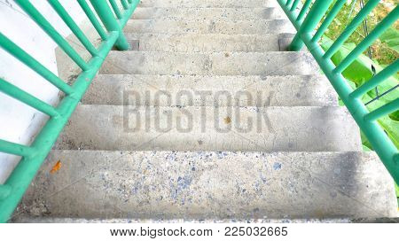 Low view of crossbridge with cement stairs and green handrails