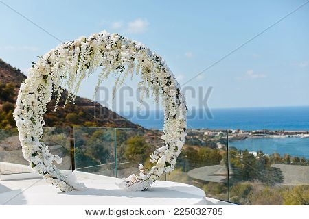 Round wedding floral arch from fresh flowers outdoors - wedding decoration.