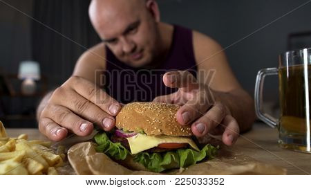 Obese man cooking big burger, overeating gourmet admiring his meal, close-up, stock footage