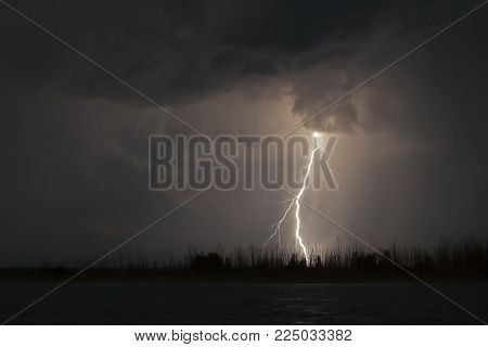 view of lightning over the lake, lightning strikes the ground, strong thunder lightning dark clouds in the sky