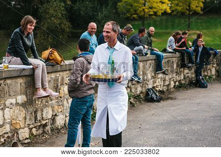 Prague, September 23, 2017: Celebrating the traditional German beer festival called Oktoberfest in the Czech Republic. A friendly smiling waiter gathers empty bottles and mugs.