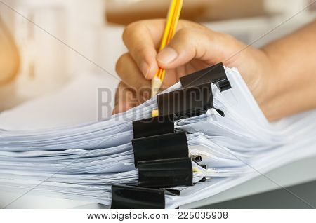 Businessman hands searching and checking write unfinished documents stacks of paper files on office desk for report papers with pencil, piles of sheet achieves clips, Document is written, drawn,presented.