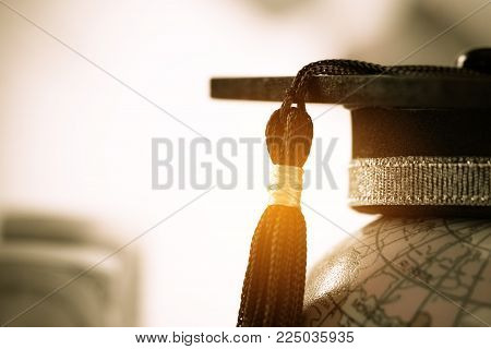 Graduate study abroad concept, Graduation cap on top Earth globe model map on laptop with Radar background. Graduate study abroad program, Back to School and Studies lead to success