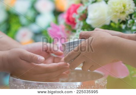 Songkran Thai festival concept : Close-up Pour water on hands of revered elders, gives blessing in Songkran day Thailand with Blur of Colorful Flowers background