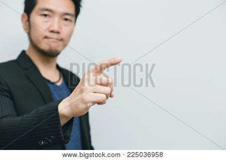 Asian business man point finger at side way to focus at white space for quote text