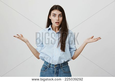 Studio shot of irritated and puzzled young european female, spreading hands and staring at camera while standing against gray background. What are you talking about, this is ridiculous.