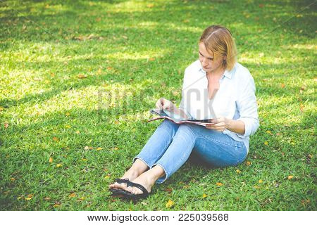 Elderly women read the book sitting in the park