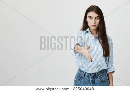 Serious-looking european woman stretching hand to greet somebody with calm and confident expression while standing against gray background. Girl makes bet with her rival, believing she will win.