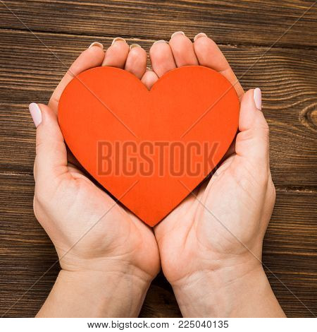 Red Heart In The Hands Of A Girl In A Sweater Close-up On A Wooden White Background.