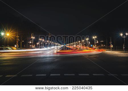 Long city street with light trails at night. Long exposure photo of straight wide road in Berlin