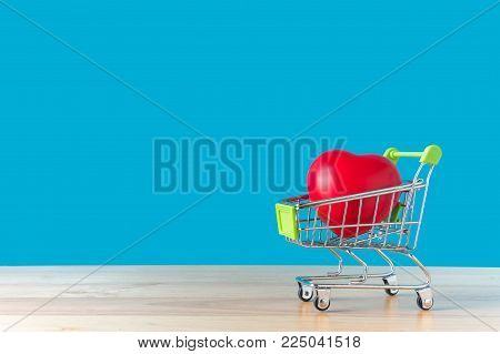 Red heart in a shopping cart on a wooden with blue background. For Valentine's Day concept. with copy space for your text message