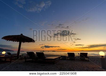 Beach umbrella and sun beds on the sea beach at sunset in thailand. with copy space for your text message