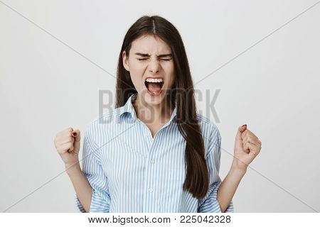 Studio portrait of angry and unsatisfied young european model showing fists and shouting with closed eyes, standing over gray background. Girl is annoyed and can not hold her emotions anymore.
