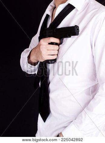 Man in black suit holding gun in hand. Secret agent, mafia, bodyguard concept.
