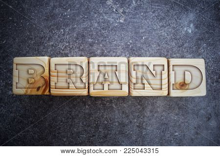 Wood blocks with letters. Wooden blocks with words. Brand - text on wooden texture blocks on grunge dark grey background.