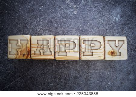 Wood blocks with letters. Wooden blocks with words. Happy - text on wooden texture blocks on grunge dark grey background.