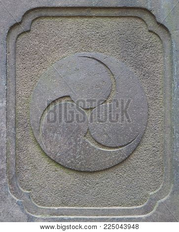 Ancient stone Japanese Shinto religion trinity symbol carving. Similar in style to the more common ying yang symbol, this is the triple trinity symbol (called Tomoe) often found near Shinto temples. The trinity may represent many things in triples includi