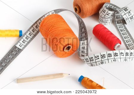 Accessories for sewing: thread, a pencil and a centimeter on a white background. Orange, brown and red bobbin thread.