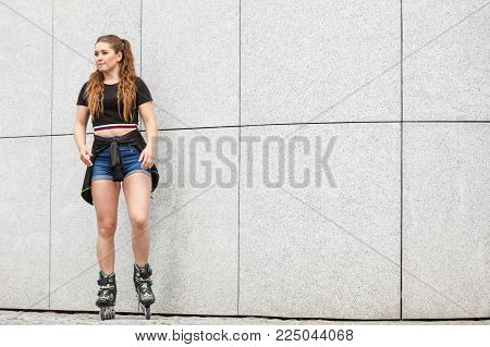 Young woman wearing roller skates standing against concrete wall in city. Female being sporty having fun during summer time.