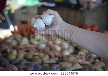Garlic Bulbs Being Purchased At A Local Food Market
