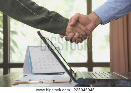 Business people shaking hands. Top view of two Business people shaking hands while standing on the desk with laptop.
