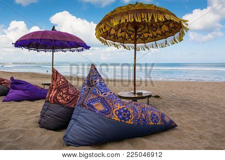 Traditional balinese umbrella and sun beds on the beach of Kuta Bali where you can relax and enjoy ocean view