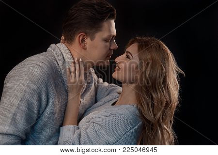 Couple intimate moment, hugging while smiling, ready to kiss each other on background with lights. Beautiful woman touching her partner looking inlolved in to his eyes. Low light