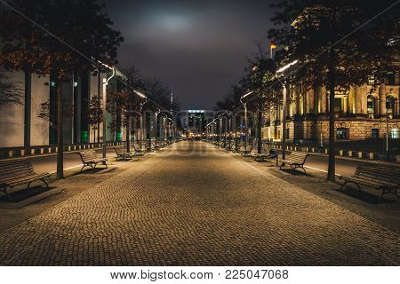 Long alley in the city at night. Picturesque night street near Reichstag building in Berlin