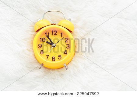 Yellow alarm clock on white wool. Late and Lazy time concept. Morning in holiday theme. Around 10 O Clock