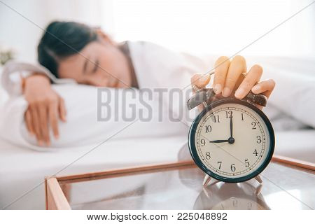 Asian young beauty woman turning off alarm clock in Morning without looking. Lazy time and Holiday concept. Bedroom theme.
