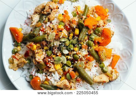 Rice with vegetables: carrots and corn, green beans, peas with pumpkin seeds and spices on white background. top view, close up, flat lay. vegetarian healthy or organic food concept