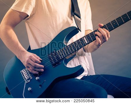 Male hands with electric guitar. Close up, part body adult person is holding instrument and playing. Hobby, music concept