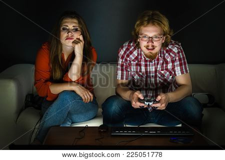 Woman is mad at her boyfriend because he play video games being addicted to gaming. Female is bored.