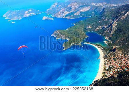 Paragliding flight over the blue lagoon of the Mediterranean Sea. Red dome of the parachute against the blue sea. Turkey. Oludeniz. Aerial photography.