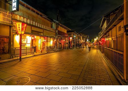 Kyoto, Japan - April 24, 2017: people walking around Gion district by night with typical Kaiseki restaurant.Hanamachi is a Japanese geisha district with okiya or geisha houses and ochaya or teahouses.