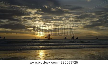 Sunset over the sea in the background boats, sailing boat, orange sky and islands. Sailing boats at sunset in the sea. Travel concept. Beautiful serene scene. Philippines, Boracay. Travel concept.
