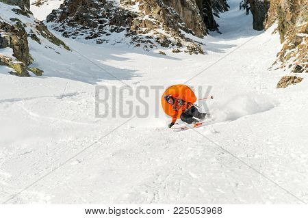 A male skier freerider with a beard descends the backcountry at high speed from the slope leaving a trail of snow powder with the opened anti-avalanche pillow ABS behind him against the background of epic rocks. The concept of freeriding culture and backc