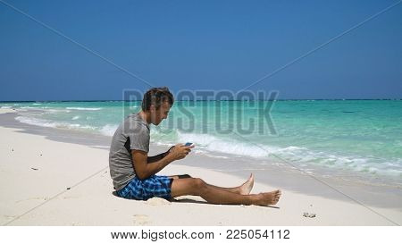Man using electronic tablet on the beach. Man sits on a sandy beach and using a tablet. Tropical beach, blue sky, clouds. Philippines, Travel concept.