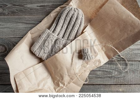 Knitted beige hat  packs in kraft paper with a small sample flat lay on wooden boards.